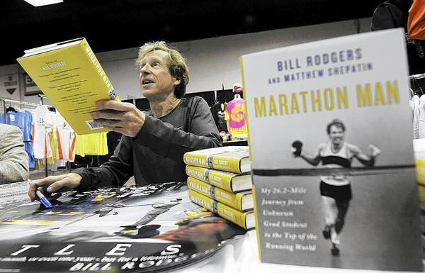 Running legend Bill Rodgers, autographs his book Marathon Man for fans attending the Healthy Lifestyles EXPO at the XL Center Friday.