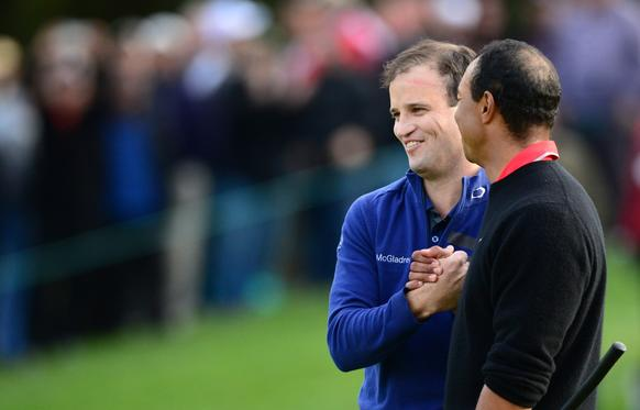 Zach Johnson is congratulated by compatriot Tiger Woods on the 18th hole after Johnson holed out to win.