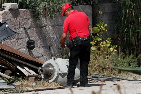 A firefighter takes photographs of radiation equipment on the patio of the family who found it in a nearby field outside Mexico City.