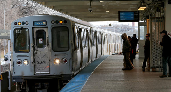 Commuters prepare to board an oncoming train at the Jefferson Park CTA Blue Line station on Dec. 5.