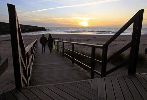 A couple walks to the beach during sunset at Lisandro beach on the Atlantic sea coast of Portugal, 25 miles north of Lisbon March 20, 2013.