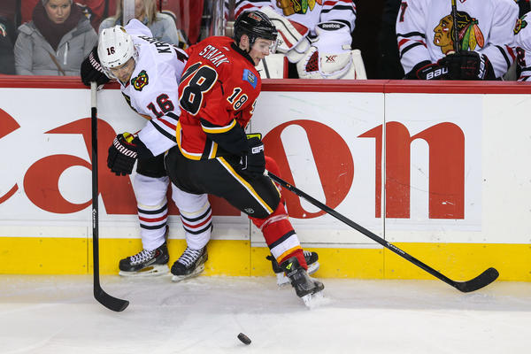 The Flames' Matt Stajan and Marcus Kruger battle for the puck during the third period at Scotiabank Saddledome.