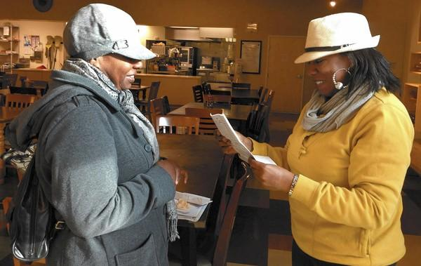 Marjorie Hauser, left, smiles as her friend Marie reads a letter telling her she's on a list for permanent housing.