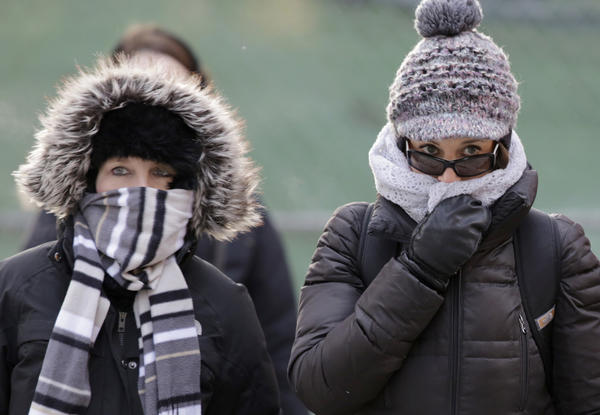 Commuters braces against the cold on North Michigan Avenue near Lake Street on Tuesday morning.