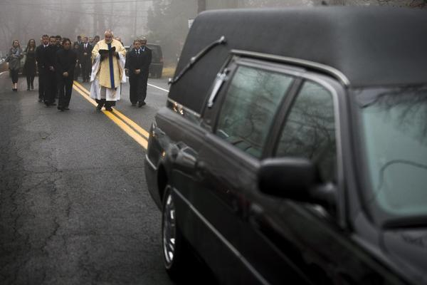 Mourners walk behind the hearse carrying the body of  James Ferrari, one of  four passengers killed Nov. 24 in a train derailment that federal investigators say could have been averted with recommended technology. Ferrari, of Montrose, NY, was buried Dec. 5.