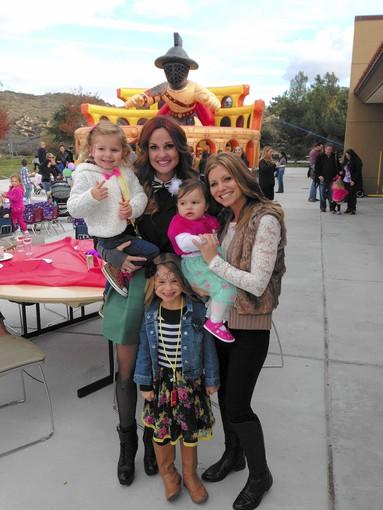 From left: Keira Taylor, 3, Kendall Taylor, 6, Briana Vartanian and Kim Taylor holding Wilhelmina Vartanian, 1, at Sunday's carnival. The event was held at the Newport Coast Community Center.