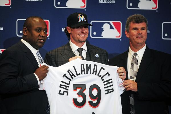 Dec 9, 2013; Orlando, FL, USA; Catcher Jarrod Saltalamacchia (center) is introduced by Miami Marlins director of baseball operations Michael Hill (left) and general manager Dan Jennings (right) during the MLB Winter Meetings at the Walt Disney World Swan and Dolphin Resort.