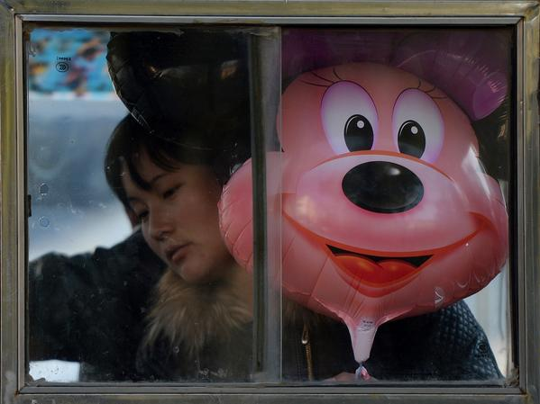 A woman rides a motorcycle taxi with a Disney character Minnie Mouse balloon in Beijing on November 7. Construction has begun on the Shanghai Disney Resort, which will be the first Disney resort in mainland China and is expected to open in late 2015.