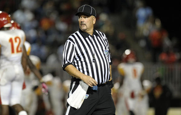Referee Carlos Carles, from Palm Beach County, works the Deerfield Beach at Miramar playoff game.