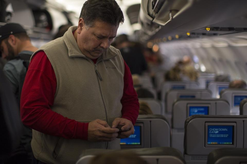 A passenger checks his cell phone December 4, 2012 before he disembarks at the Long Beach, California airport.
