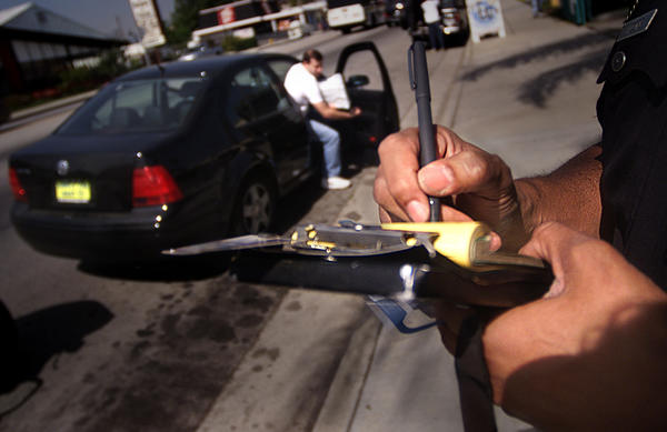 An LAPD officer writes a ticket to a driver who didn't stop for pedestrians on Reseda Boulevard in Northridge.