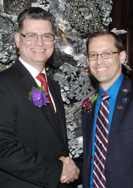 Incoming Burbank Association of Realtors president Julian Munoz, left, receiving congratulations from outgoing president Eric Benz at last week's holiday celebration.