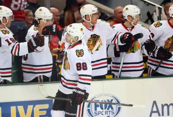 Patrick Kane celebrates his first-period goal with the Blackhawks bench.