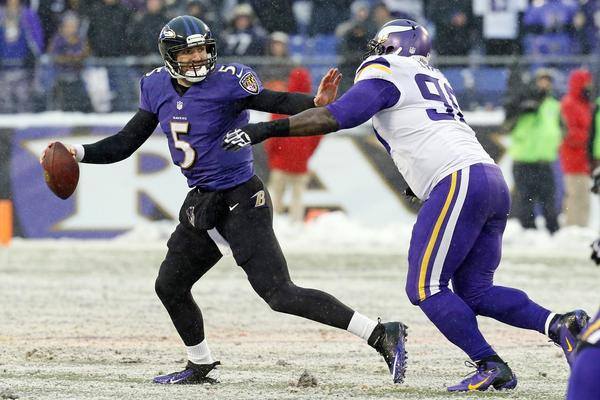 Ravens quarterback Joe Flacco looks to pass as Vikings tackle Fred Evans chases him down.