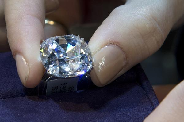 A Christie's employee holds a cushion-cut-D-color internally flawless diamond ring of 26.72 carats December 6, 2013 at Christie's in New York. The diamond ring is part of the Magnificent Jewels auction scheduled for December 10. AFP PHOTO/Don EmmertDON EMMERT/AFP/Getty Images ORG XMIT: