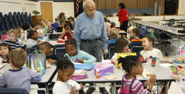 Reuben Price, 91, has been a cafeteria monitor at Armstrong Elementary School in Hampton for about 10 years. He interacts with each student, giving a high five or opening the top of a food container the child is having trouble with.