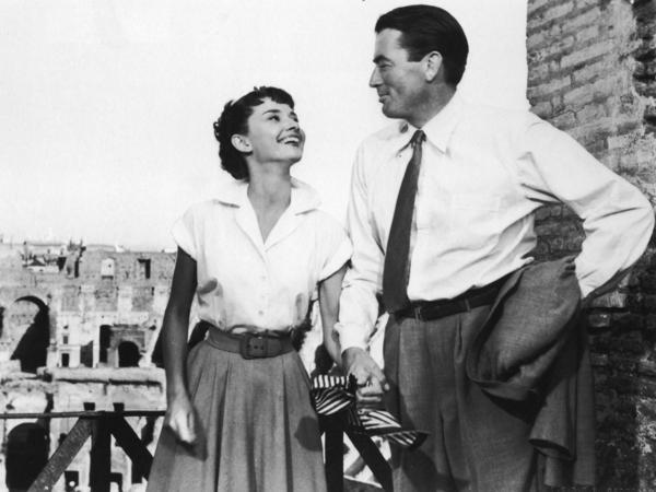 """Belgian-born actor Audrey Hepburn holds the hand of American actor Gregory Peck in a still from the film """"Roman Holiday,"""" directed by William Wyler in 1953."""