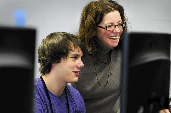 Tyler Kearney, 19, of Vernon, left, and Kathy Chapdelaine, Director of Enfield Adult Education, right, look at a computer-based GED practice test in the computer lab at the Alcorn School.
