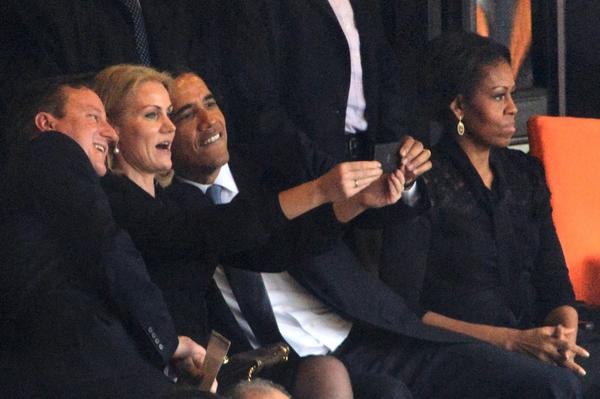 President Barack Obama and British Prime Minister David Cameron pose for a picture with Denmark's Prime Minister Helle Thorning Schmidt next to US First Lady Michelle Obama during the memorial service of South African former president Nelson Mandela at Soccer City in Johannesburg.