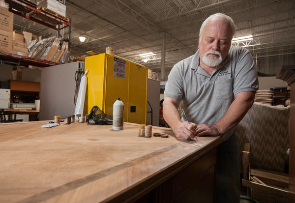 Furniture restorer Jim McCullough works on Thurgood Marshall's office desk from the Department of Justice.