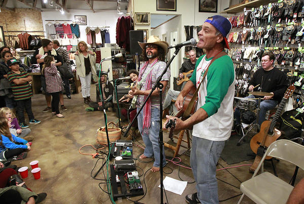 Ken Garcia, left, and Nick-I Hernandez, sometimes known as Common Garcia, entertain the holiday masses at the Hobie Store during Hospitality Night in downtown Laguna on Friday.