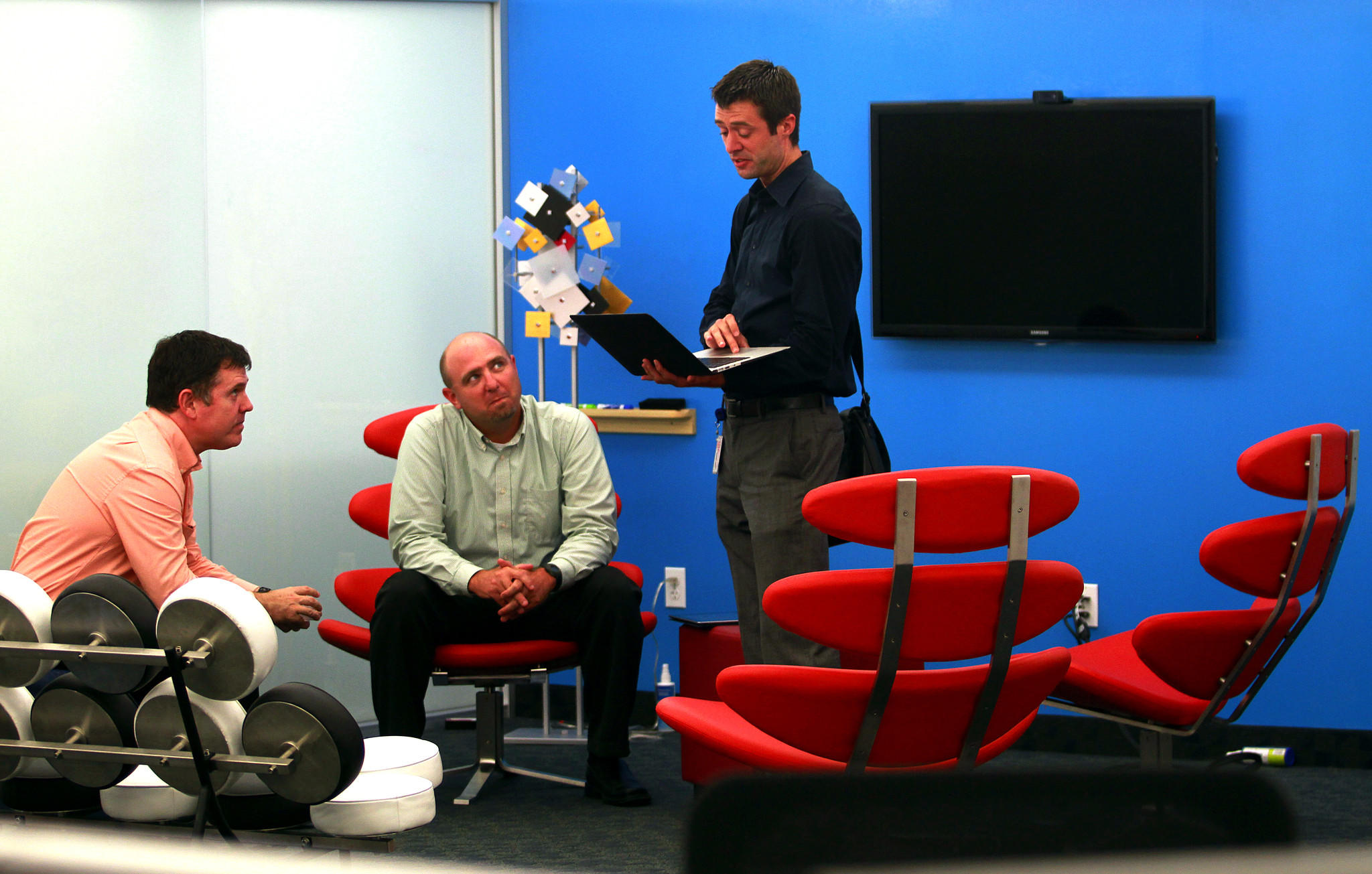 Michael McKiernan, vice president of Business Technology Solutions and Trenton Cycholl talk with Sebastian Barnes in the Pop Art front porch of Citrix's Ft Lauderdale office in 2012.