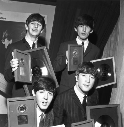 "Ring Starr, George Harrison, John Lennon and Paul McCartney hold up silver discs, gifts from a record label, to mark the sales of their ""Please Please Me"" LP and ""Twist and Shout,"" which went on to become the best-selling EP of all time. Jean-Michel Guesdon and Philippe Margotin's book ""All the Songs"" details the story of every Beatles song ever released."