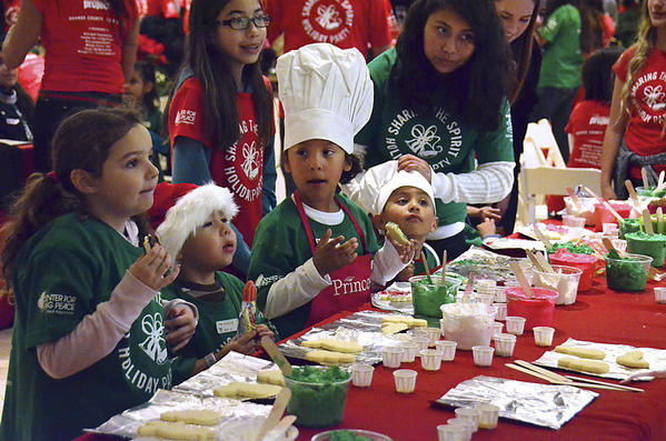 "Several kids decorate cookies at the Christmas cookie decorating station which was one of the most popular events during the ""Sharing the Spirit"" holiday party"" in Santa's Village at South Coast Plaza on Friday. The event was organized and put on by the Festival of Children Foundation and The Happiness Project and included around 600 underprivileged kids from Anaheim, Costa Mesa, Garden Grove, and Santa Ana, among other Orange County cities. Each child was given a gift bag upon arrival."