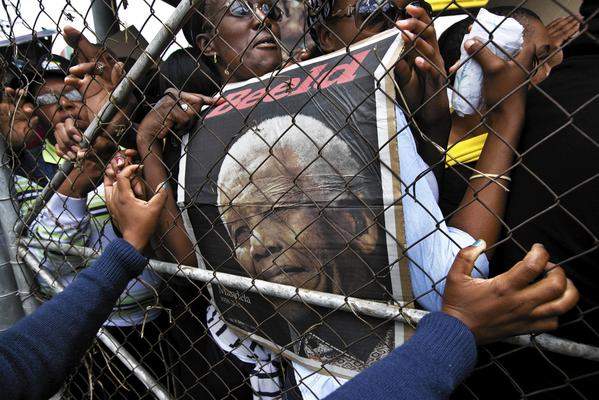 A police officer pushes against a metal gate to stop a crowd surging toward buses headed for the viewing of the casket of Nelson Mandela lying in state in Pretoria, South Africa, on Dec. 11.