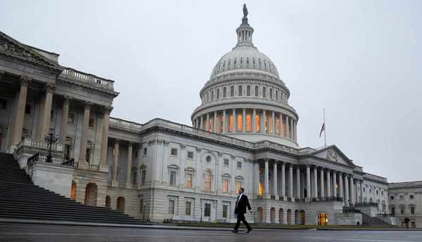 A man walks past the U.S. Capitol Building in Washington December 2012.