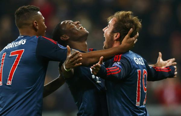Bayern Munich's Mario Goetze (R) celebrates Jerome Boateng (L) and David Alaba after scoring a goal against Manchester City during their Champions League Group D soccer match in Munich December 10, 2013.