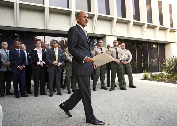 Los Angeles County Sheriff Lee Baca arrives at a news conference after the FBI released results of a federal probe on Monday.