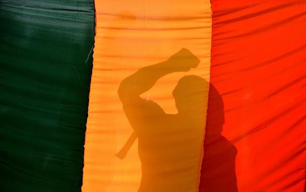 An Indian gay-rights activist gestures behind a flag during a protest against the Supreme Court ruling reinstating a ban on gay sex.
