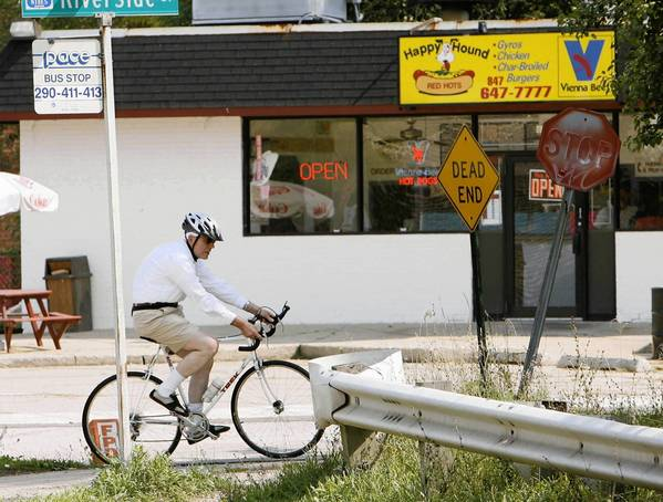 A bicyclist crosses Touhy Avenue in Niles.