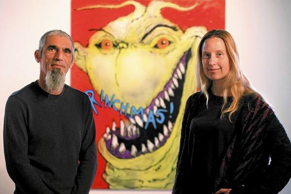 "Co-owners Mark Weiner, left, and Torrey Cook pose for a portrait in front their holiday-themed exhibit titled ""Straight Outta Whoville : The Night Before Grinchmas"" at the Artists Republic For Tomorrow gallery in Laguna Beach on Wednesday."