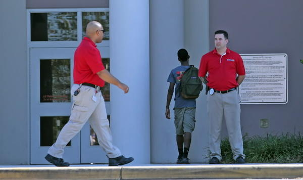A students arrives on campus as members from a security firm, wearing red shirts, were hired as an increased security measure at West Orange High School on December 5, 2013.