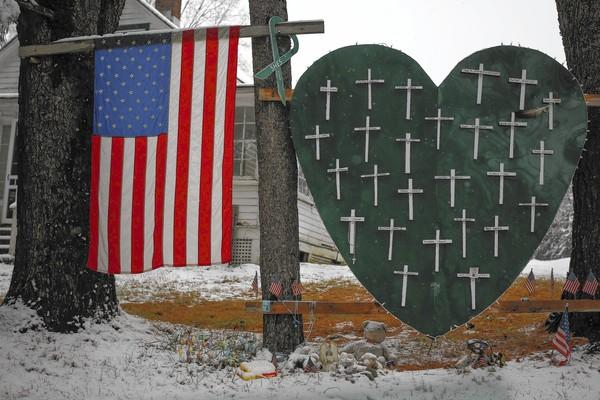 A memorial honoring the victims killed in the Sandy Hook Elementary School shooting is seen outside a home in Newtown, Conn., on Tuesday, nearly one year after the attack.