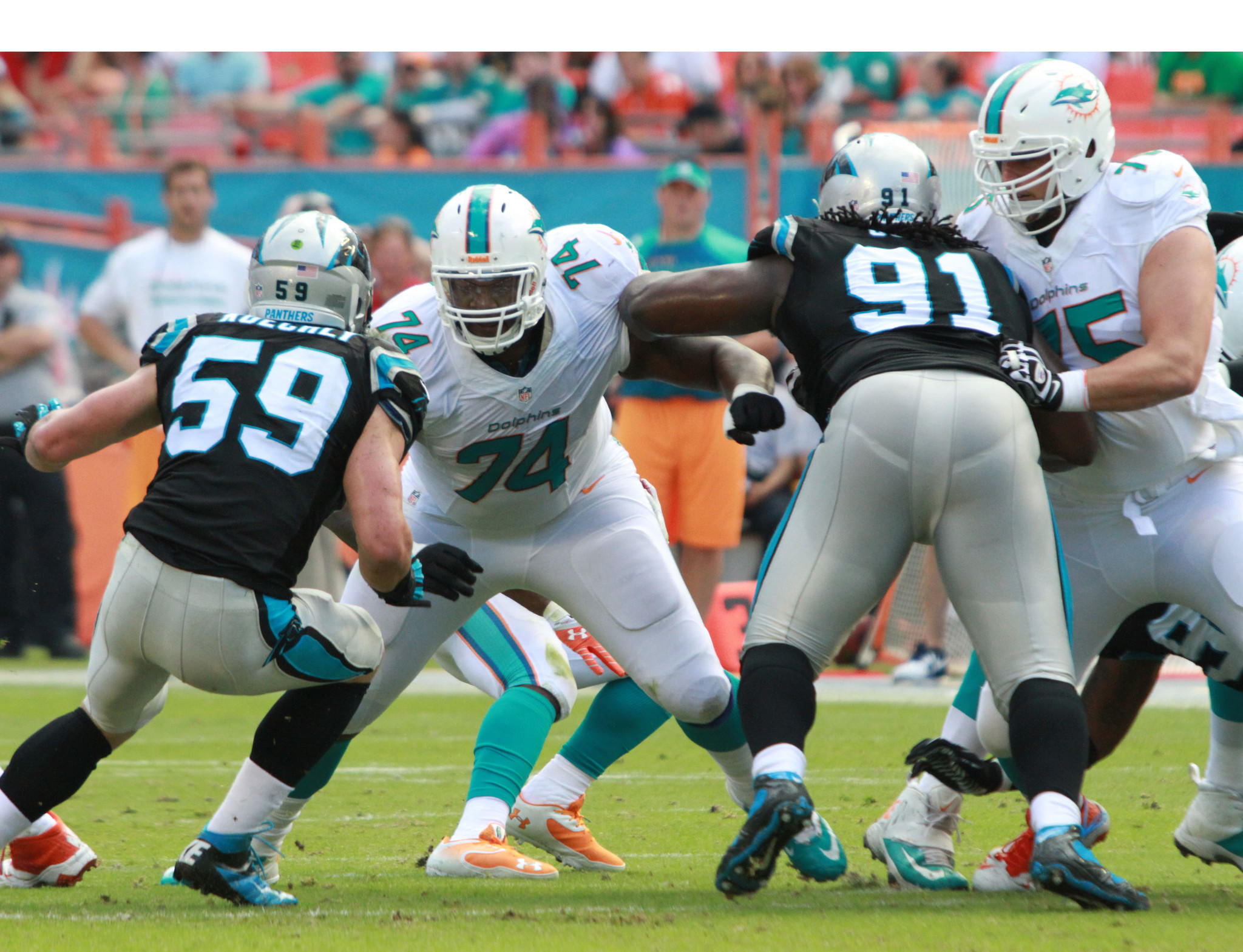 John Jerry uses his massive frame to block Luke Kuechly and Colin Cole from the opposition.