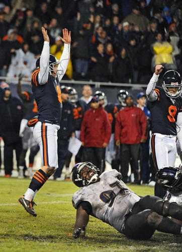 Ravens defensive lineman Arthur Jones, bottom, sits on the ground as Chicago Bears holder Adam Podlesh celebrates after Robbie Gould's game-winning field goal.