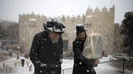 Snow closes roads in Israel, is a source of wonder in Egypt