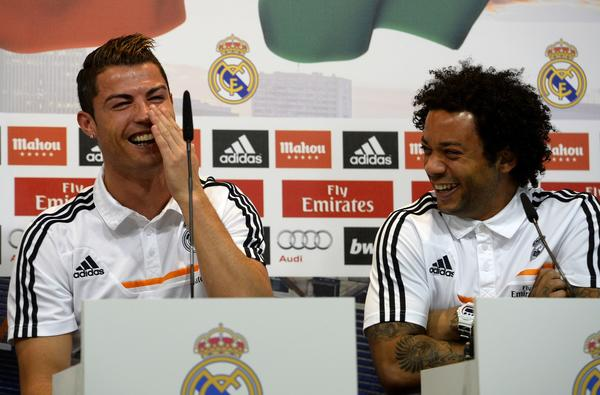 Portuguese forward Cristiano Ronaldo (L) and Brazilian defender Marcelo laugh as they give a press conference with their temmates to give their thoughts on 2014 World Cup draw, at the Valdebebas training ground in Madrid on December 8, 2013.