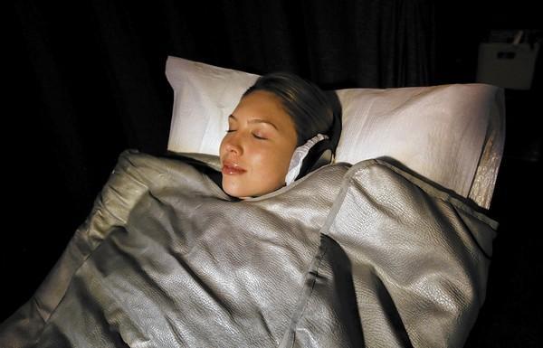 Erica Eynon, who works at Shape House, takes a sweat treatment using a heated sleeping bag.