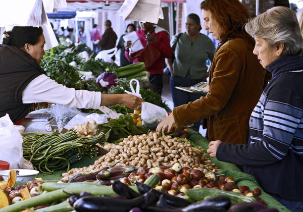 People shop for fresh vegetables and fruits at the downtown Farmer's Market on Brand Blvd. in Glendale on Thursday, Oct. 10, 2013. In 2014, the city of Glendale will hand over the operation of the Farmer's Market to the Downtown Glendale Association.