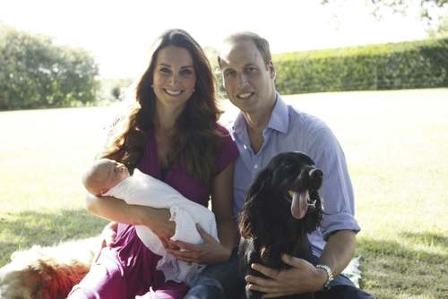 Britain's Prince William and his wife Catherine, Duchess of Cambridge, pose in the garden of the Middleton family home in Bucklebury, southern England, with their son Prince George, cocker spaniel Lupo (R) and Middleton family pet Tilly.