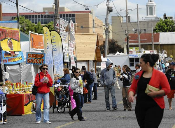 People walk the grounds of Mayfair outside the Agri-Plex at the Allentown Fairgrounds last May.