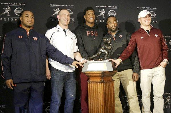 Heisman finalists (from left) Auburn running back Tre Mason, Northern Illinois quarterback Jordan Lynch, Florida State quarterback Jameis Winston, Boston College running back Andre Williams and Texas A&M quarterback Johnny Manziel gather around the trophy Friday in New York.