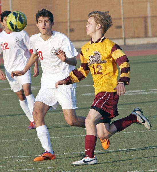 Glendale High's Menua Nazarian, left, and La Canada's Andrew Meeker go for the ball in Friday's match.