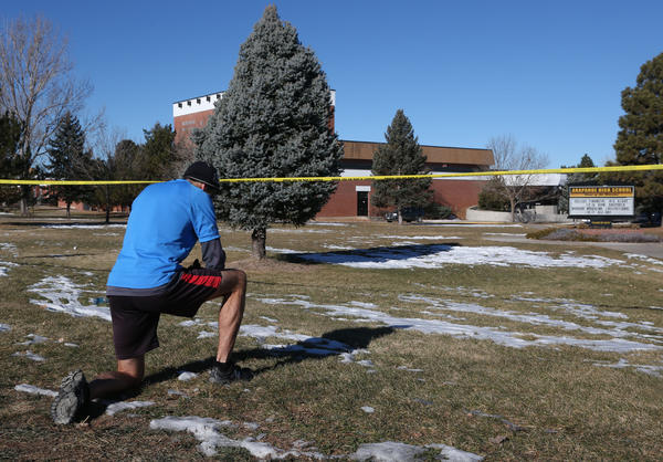 Sean Sweeney, a runner who lives near Arapahoe High School in Centennial, Colo., pauses Saturday to say a prayer outside the school that was terrorized by a gunman Friday.
