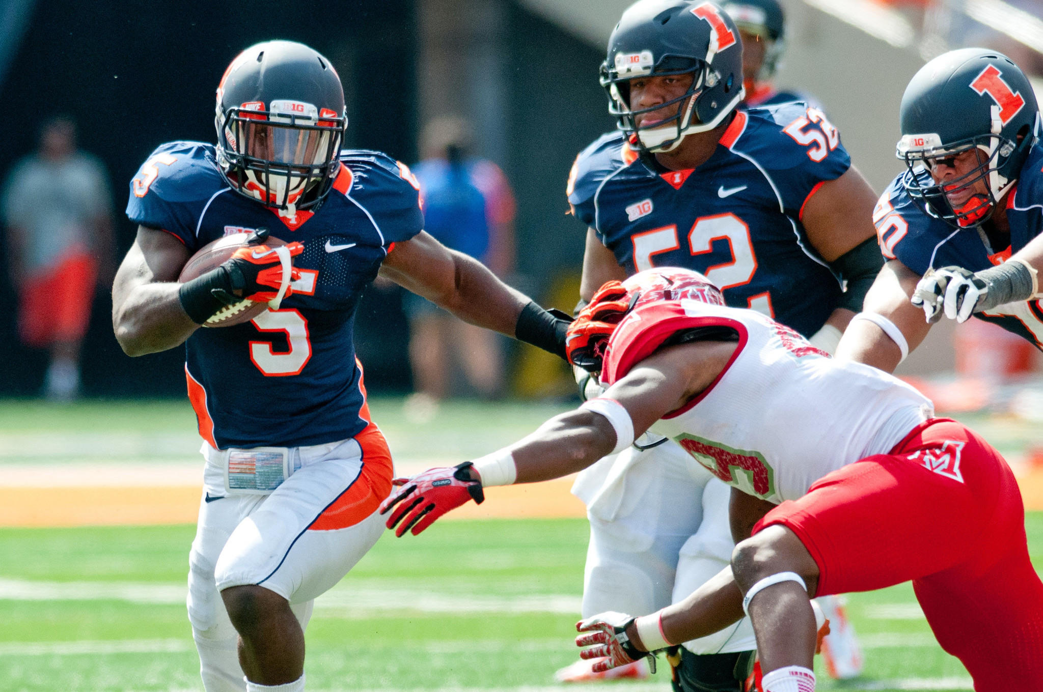 Illini running back Donovonn Young avoids a tackle by Miami's T.J. Williams during the third quarter at Memorial Stadium.