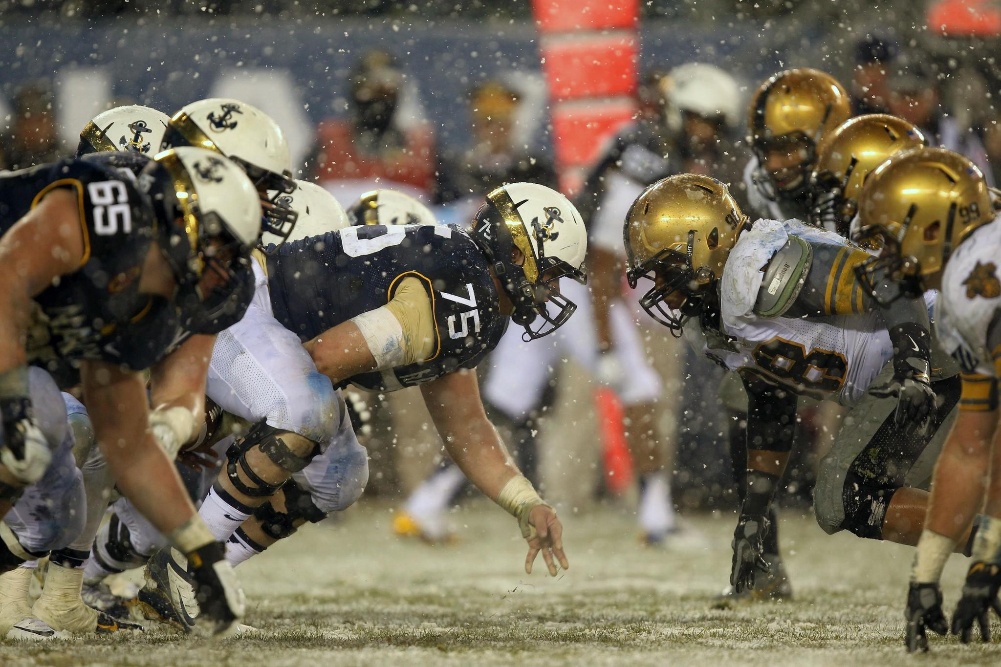 Center Tanner Fleming (75) and the Navy line prepare to collide with defensive lineman Richard Glover (98) and the Army defense at the line of scrimmage during the first half at Lincoln Financial Field.